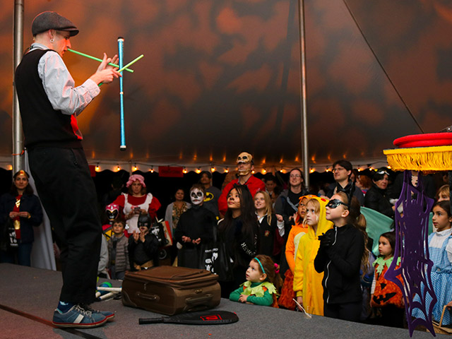 children dressed in costumes watching a magician on stage