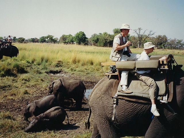 photo of man and woman with elephants in Africa