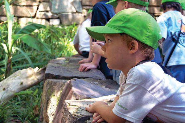 child with green hat at animal exhibit
